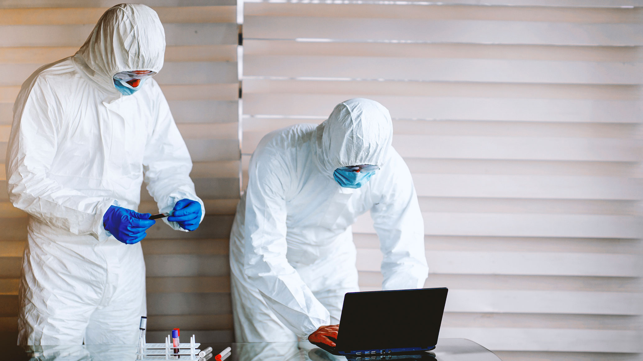 Two people in chemical suits examining test tubes and using a laptop