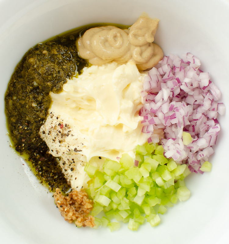 Overhead shot of egg salad ingredients in a white bowl