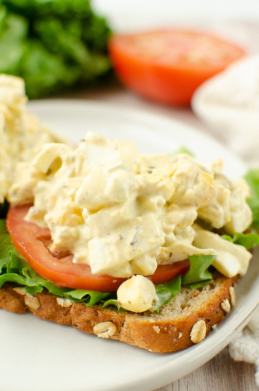 Open faced egg salad sandwich on a white plate; lettuce and tomato in the background