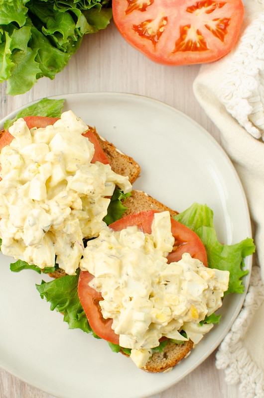 Overhead of open faced egg salad sandwich on a white plate; lettuce and sliced tomato in the background