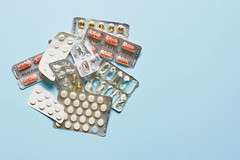 Medication and pills on light blue background