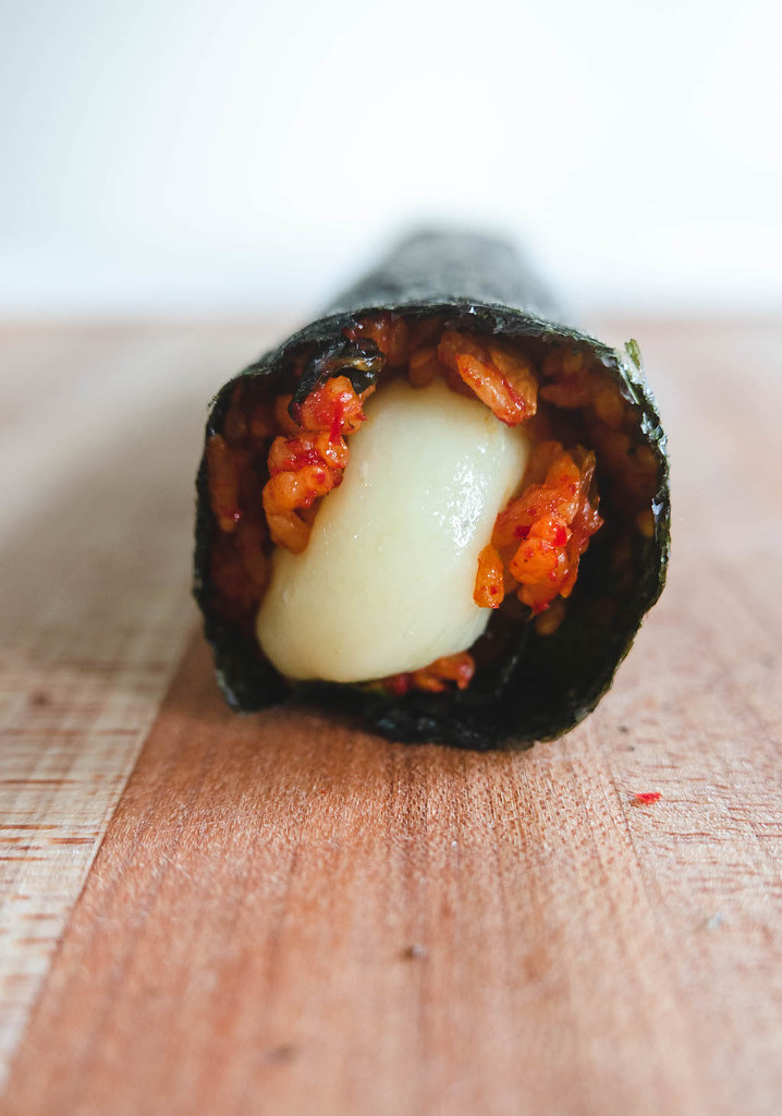 A roll of cheese kimbap. The cheese is oozing out of the roll.