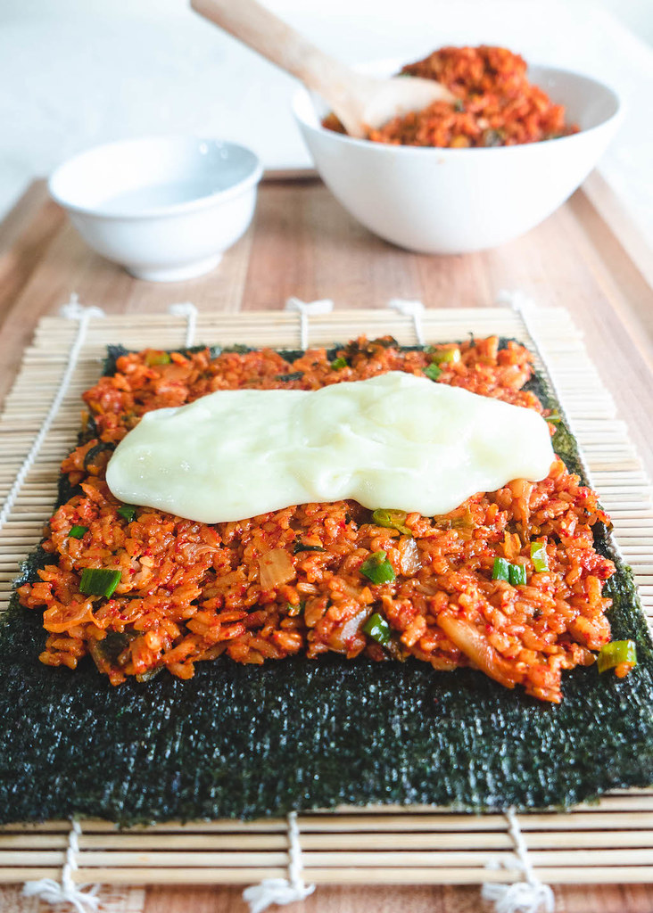 Kimchi fried rice spread over dried seaweed. Then, cheese poured overtop the kimchi fried rice.