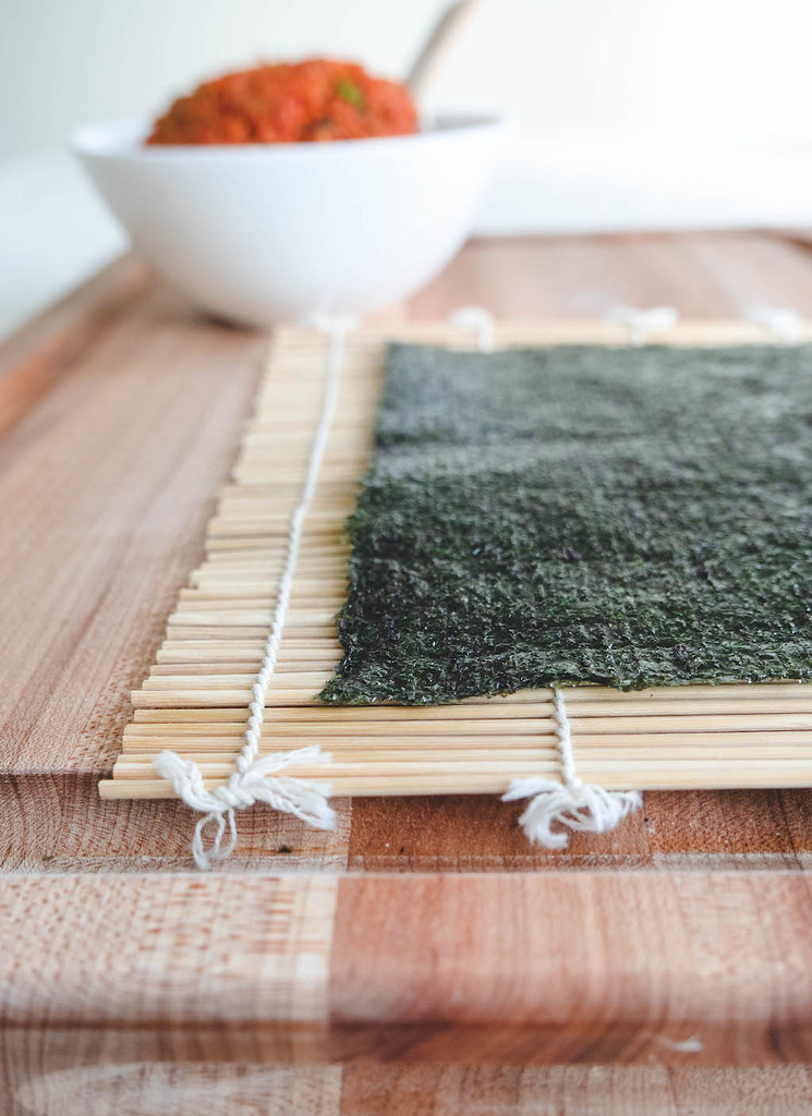 Dried seaweed on a bamboo mat. The kimchi fried rice is sitting in the background.