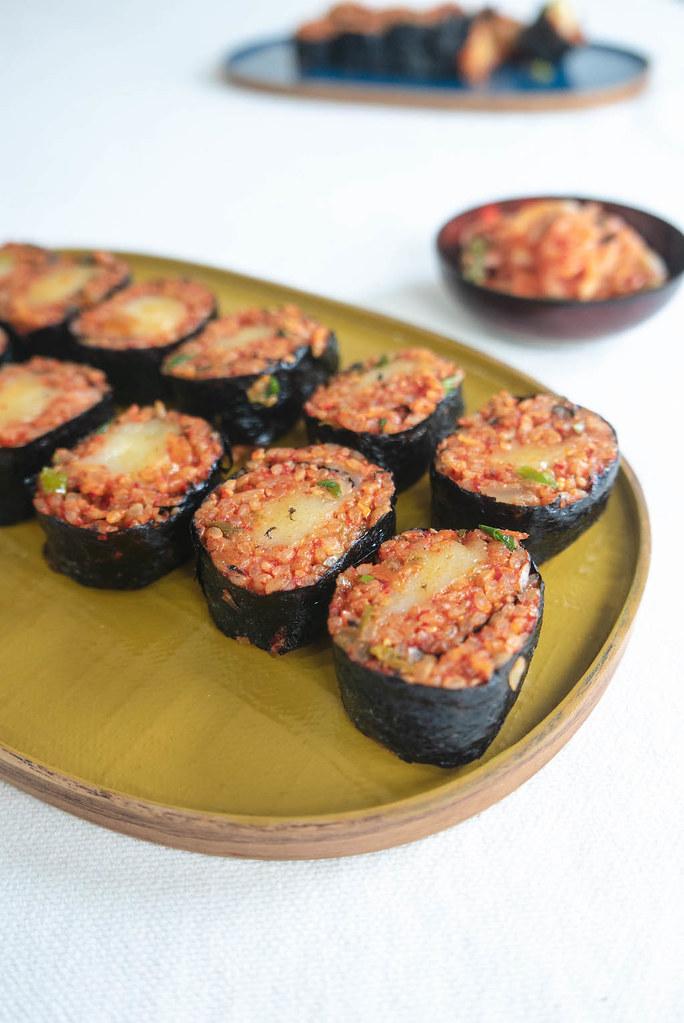 Sliced kimbap sitting on a yellow tray.