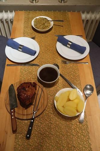 Krustenbraten mit Soße zu Salzkartoffeln und Sauerkraut (Tischbild)