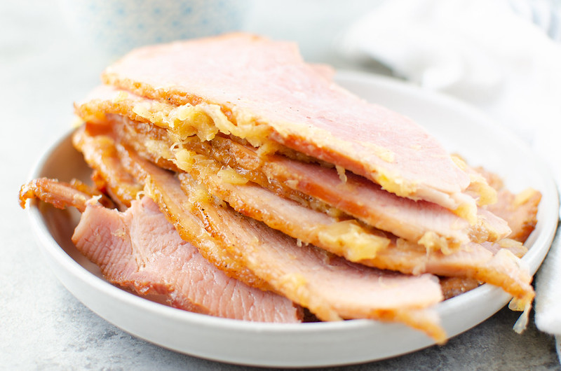Slices of pineapple brown sugar glazed ham on a white plate