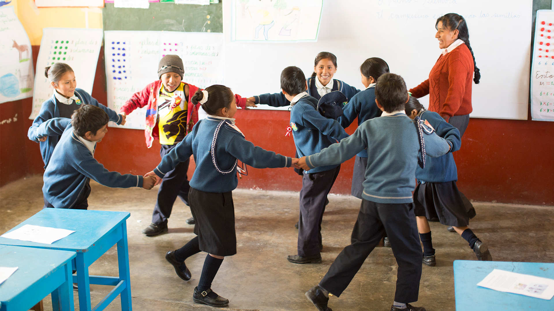 A group of children holding hands in a circle with a teacher playing a game