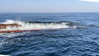 Photo of barge being sunk into the ocean, to serve as artificial reef