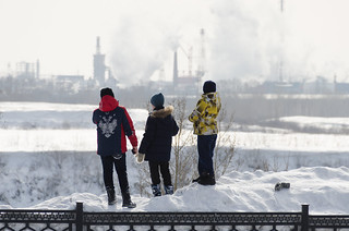 3 boys looking across river Tom at industrial plants in Kemerovo, Russia | by justinwyllie
