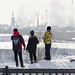 3 boys looking across river Tom at industrial plants in Kemerovo, Russia