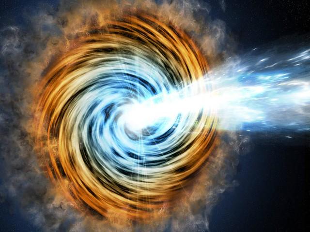 VCSE - Egy blazár egy nagyon nagytömegű fekete lyuk egy aktív galaxis közepén, amire közel, de nem pontosan a fekete lyuk által kilövellt jetről nézünk rá. (Fehéres kiáramló anyagsugár.) A fekete lyuk körül egy spirális anyagbefogási korong van, ami a közelében elhaladó, a lyuk árapályereje által széttépett csillagok és csillaghalmazokból jött létre. A fényességváltozást a kilövellt nyaláb (ang. jet) fényesésgingadozásai okozzák, mert az anyagutánpótlás nem teljesen állandó és folyamatos. - Forrás: wikipedia