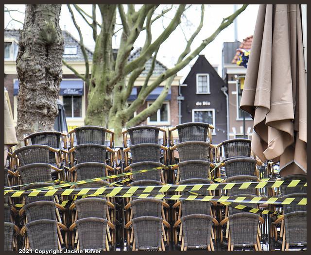 Lege terrassen en opgestapelde stoelen.