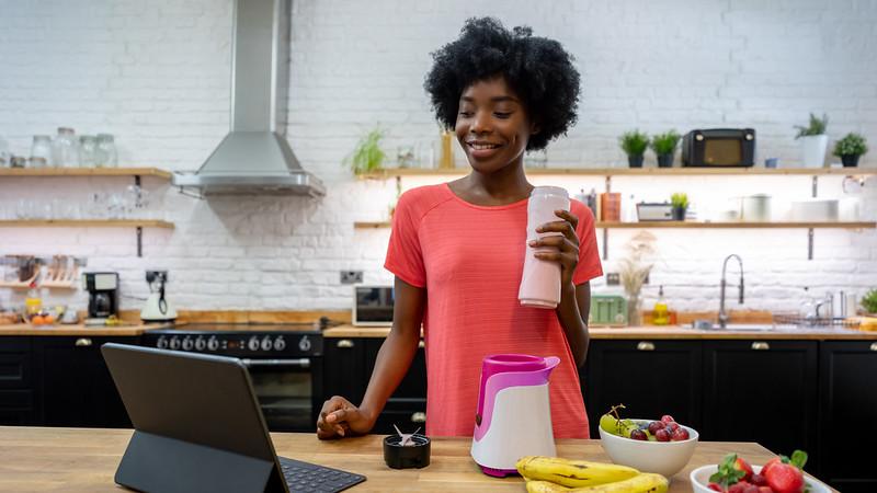 一个女人站在厨房里喝着冰沙,一边用笔记本电脑看视频