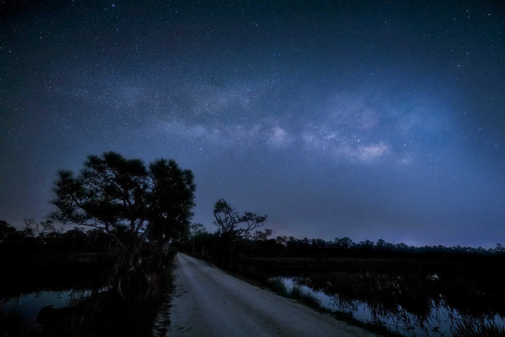 The Milky Way reflected in marsh and dirt road at Babcock Wildlife Management Area near Punta Gorda, Florida