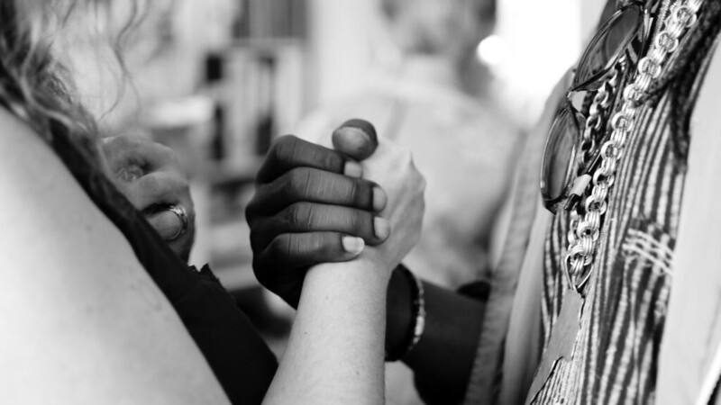 People from different ethnic backgrounds holding hands in black and white setting