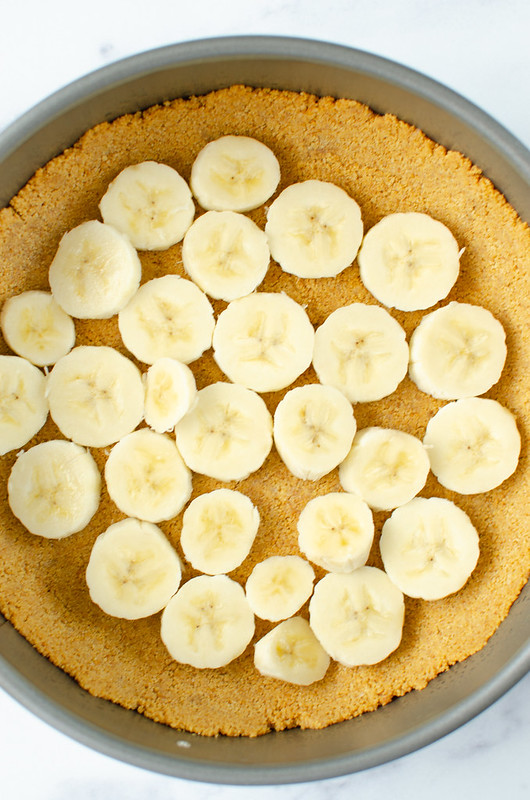 Sliced bananas in a graham cracker crust in a springform pan