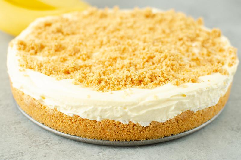 Horizontal photo of banana cream cheesecake; layers of graham cracker crust, cheesecake, and whipped cream with a graham cracker crumb topping