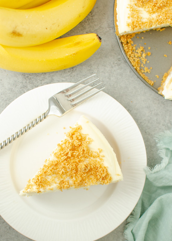 Overhead shot of banana cheesecake and a fork on a white plate with a green cloth napkin beside it; bunch of bananas and the rest of the cheesecake on a pan in the background