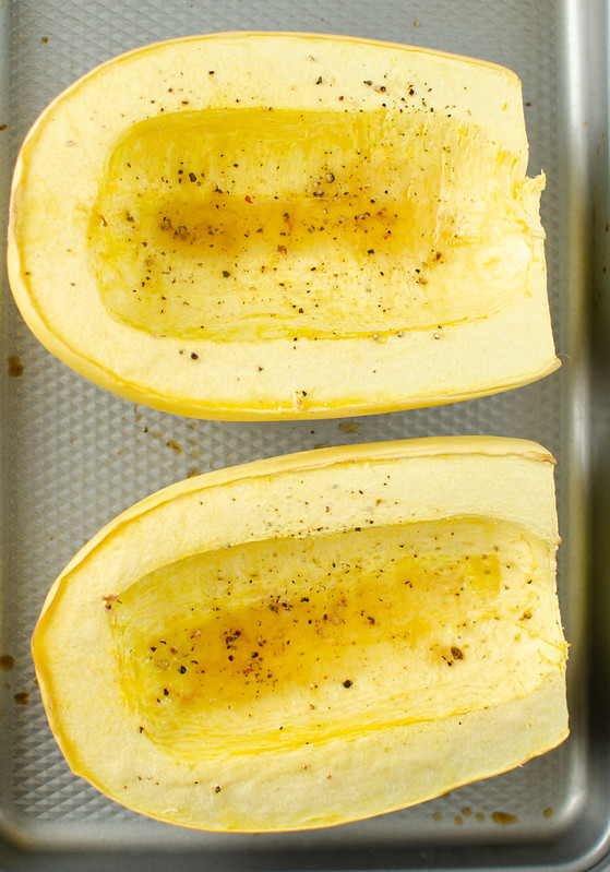 Two halves of spaghetti squash after baking on a rimed baking sheet with black pepper sprinkled on top