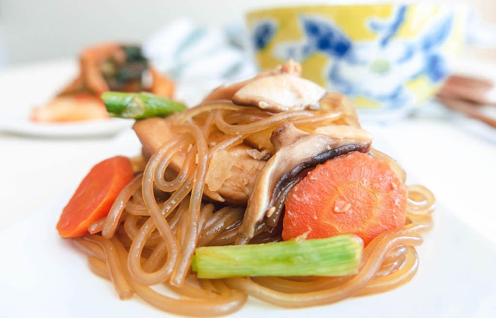 A photo of Andong jjimdak--carrots, green onions, chicken, mushrooms, potatoes, and noodles.