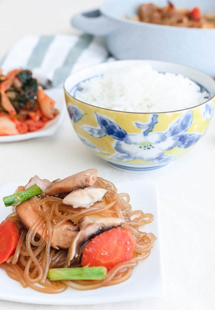 A single serving of andong jjimdak with a bowl of rice, kimchi, and the pot of jjimdak.