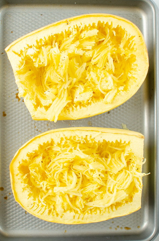 Spaghetti squash with the strands separated on a rimmed baking sheet