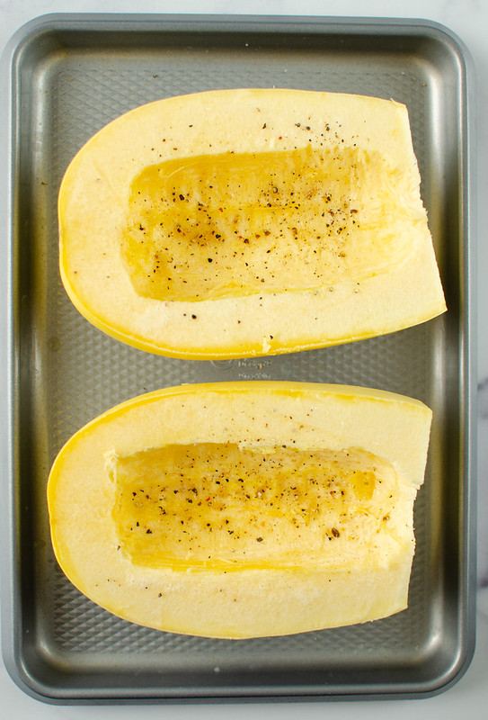 Two halves of raw spaghetti squash sprinkled with black pepper on a rimmed baking sheet