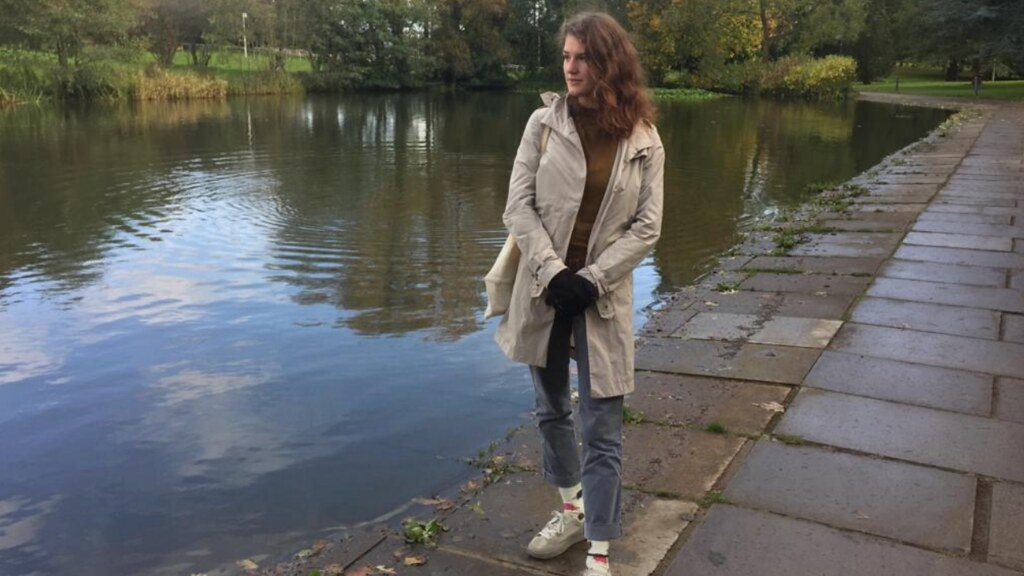 A photo of Flavia Olivieri standing by a pond.