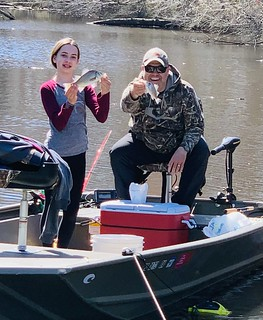 Photo of girl with her father, holding white perch they caught