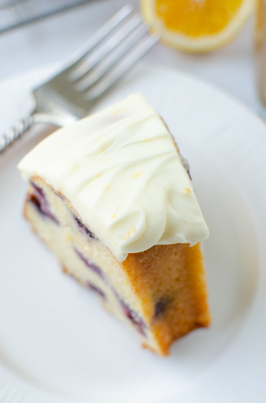 Overhead shot of meyer lemon blueberry budnt cake with a thick layer of cream cheese frosting on a white plate; fork in the background