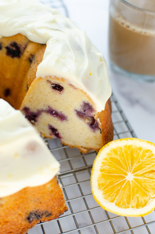 Meyer lemon blueberry bundt cake on a wire rack with a slice taken out of it; halved lemon and a mug of coffee in the background