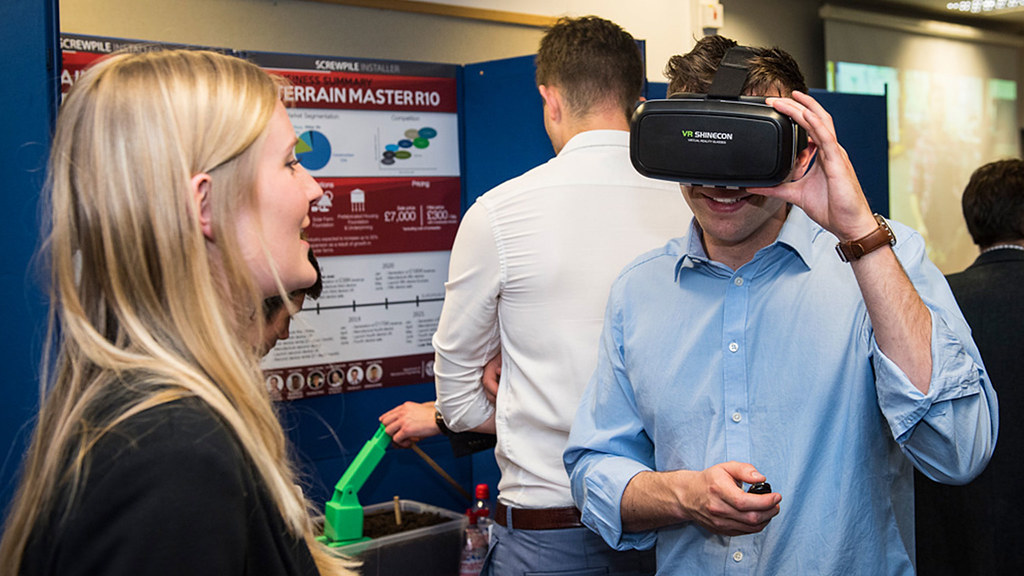 A student puts on a virtual reality headset in front of an exhibition booth.