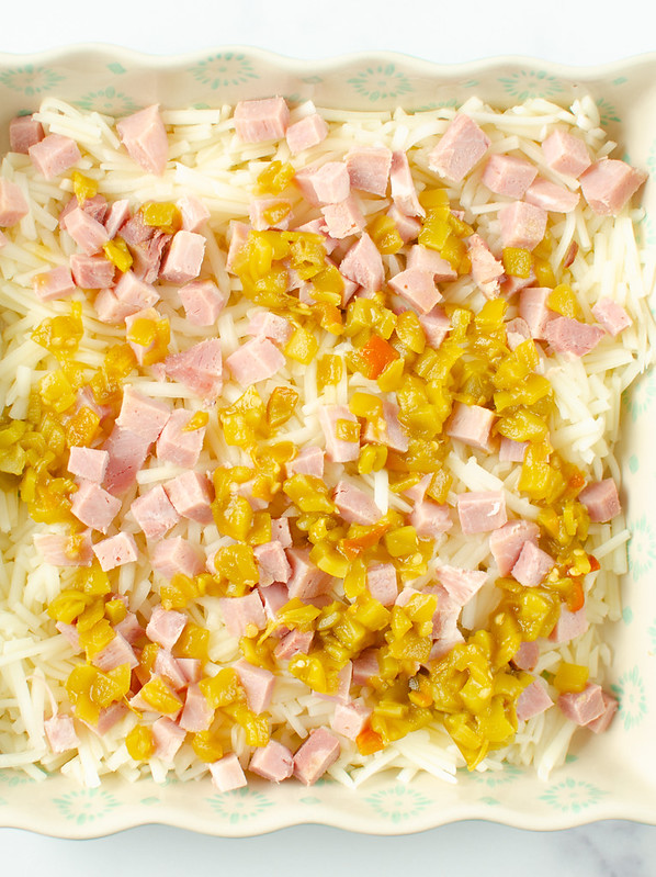 Layers in hashbrowns, ham, and diced green chilese in a casserole dish