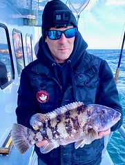 Photo of man on a boat holding a tautog