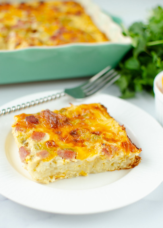 Slice of ham breakfast casserole on a white plate; fork, cilantro, and casserole dish in the background