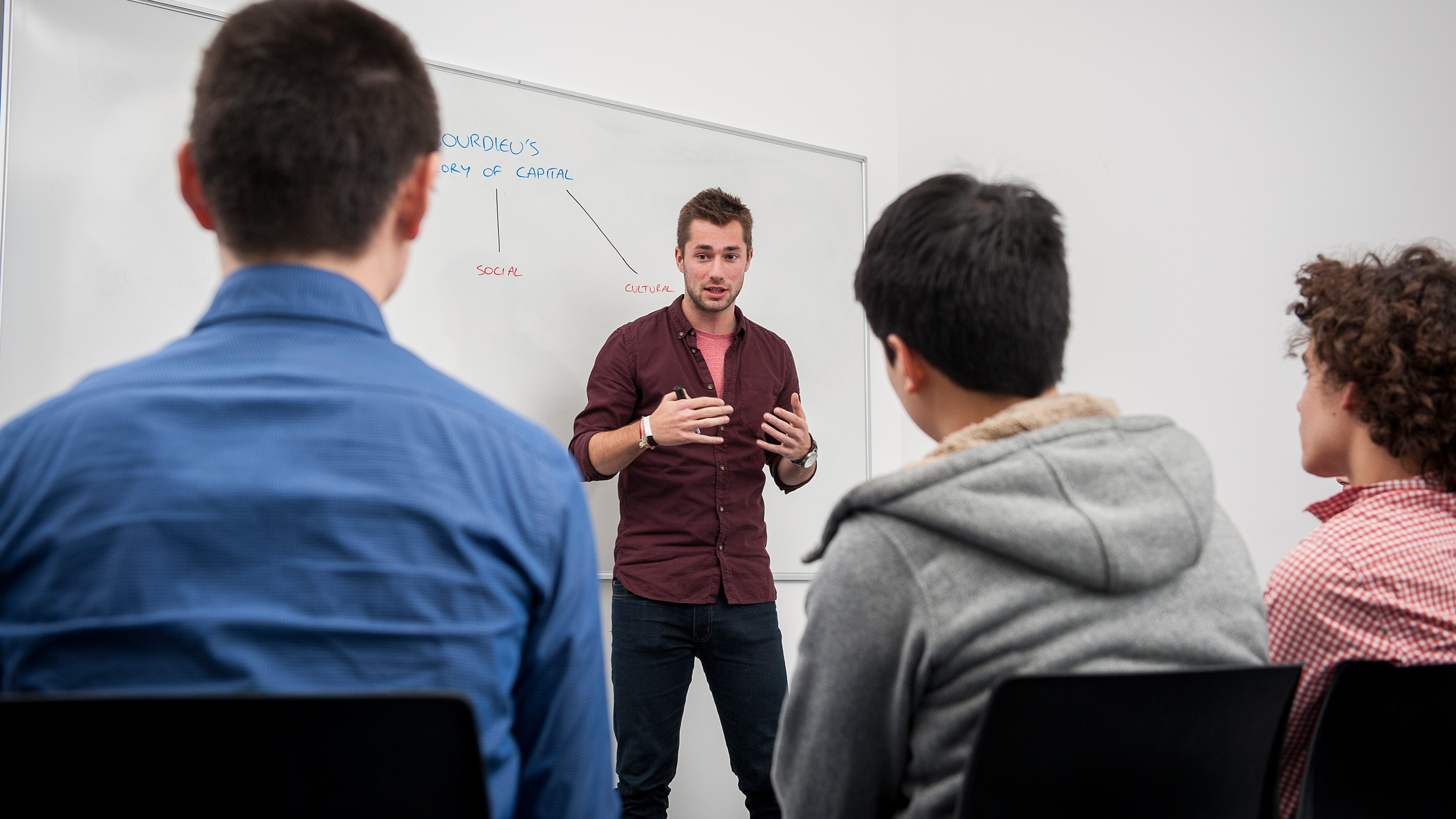 Student standing by a whiteboard delivering a presentation to three other students.