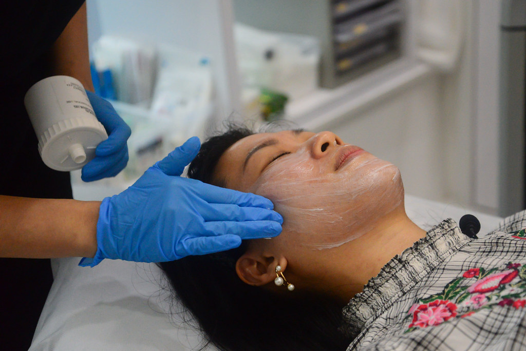 Clinic assistant applying numbing cream on my face