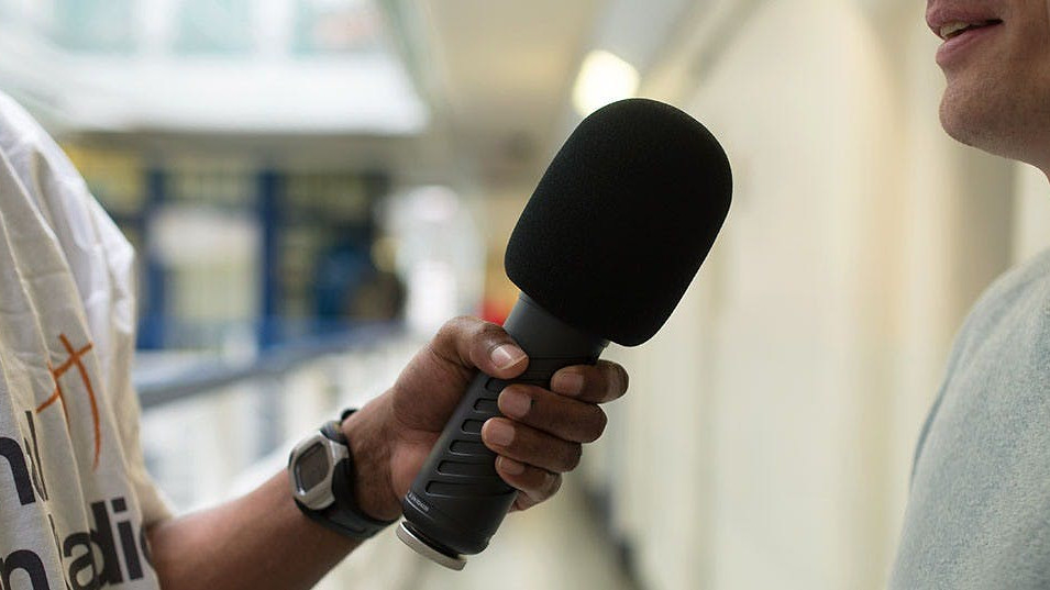 Two people standing next to each other in conversation with one person holding a microphone in their hand to record it