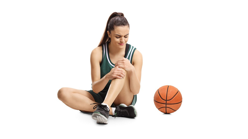 Female basketballer clutching knee, illustrating an ACL injury.