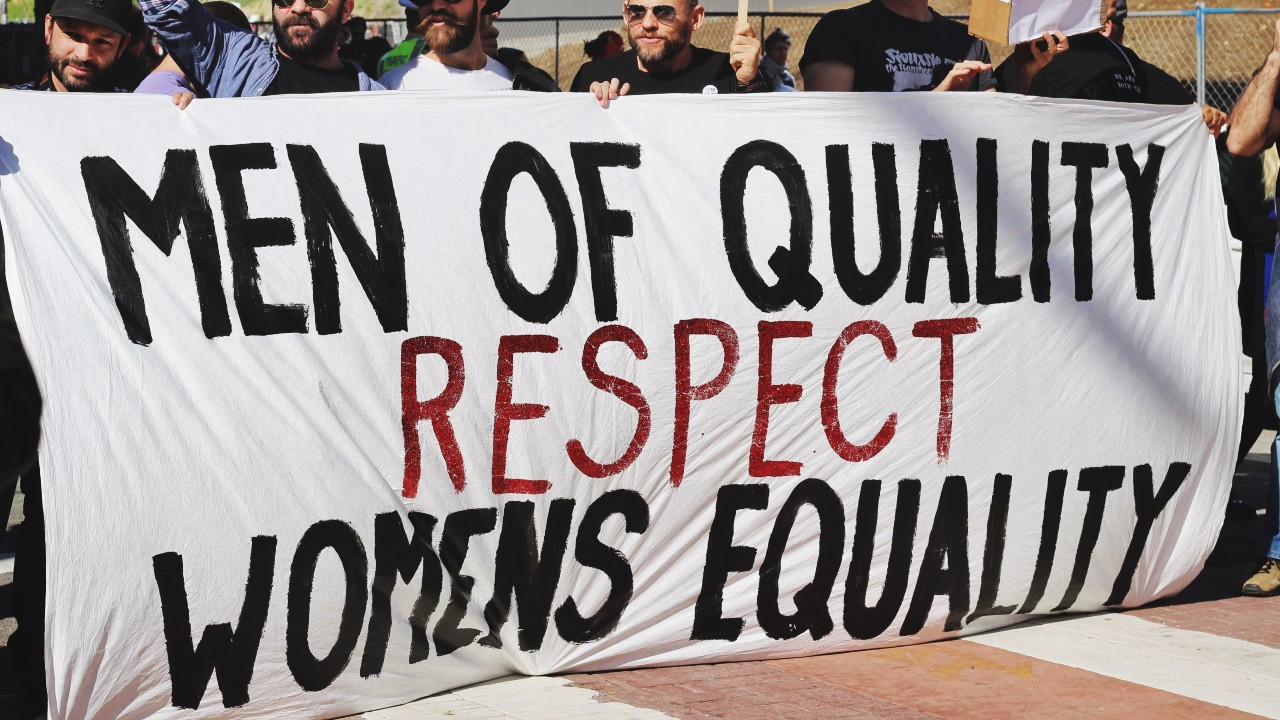 Men with a banner saying 'Men of quality respect women's equality'