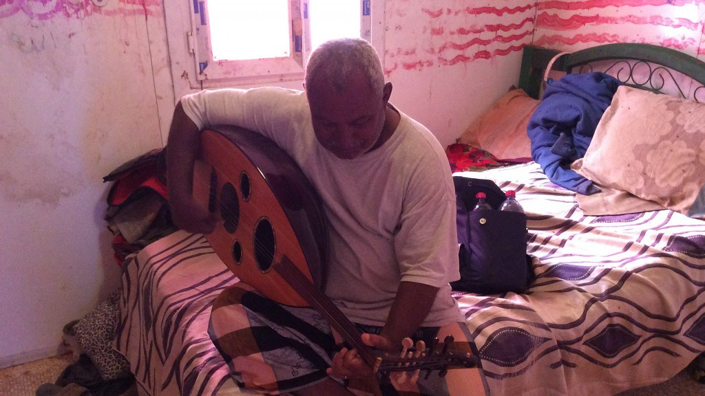 An black man playing a Oud while sitting on a bed in a small run down room