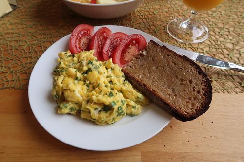 Rührei zu Butterbrot und aufgeschnittener Tomate