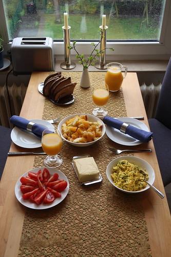Frühstück mit Obstsalat und Rührei sowie Tomaten zu aufgetoastetem Majannebrot