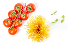 Spaghetti, a branch of tomatoes and basil leaves, top view