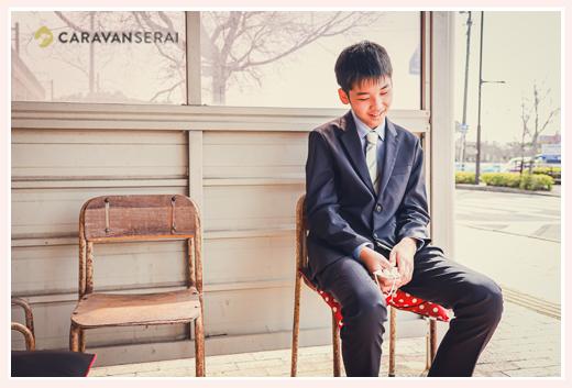 バス停の待合所でバスを待つ男の子