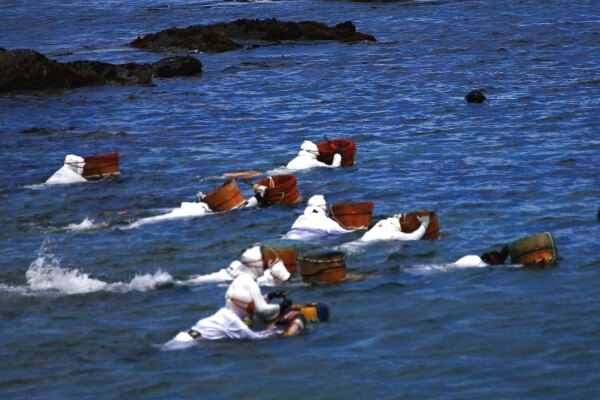 11 people wearing white suits swim in the ocean, each of them is swimming with a wooden bucket