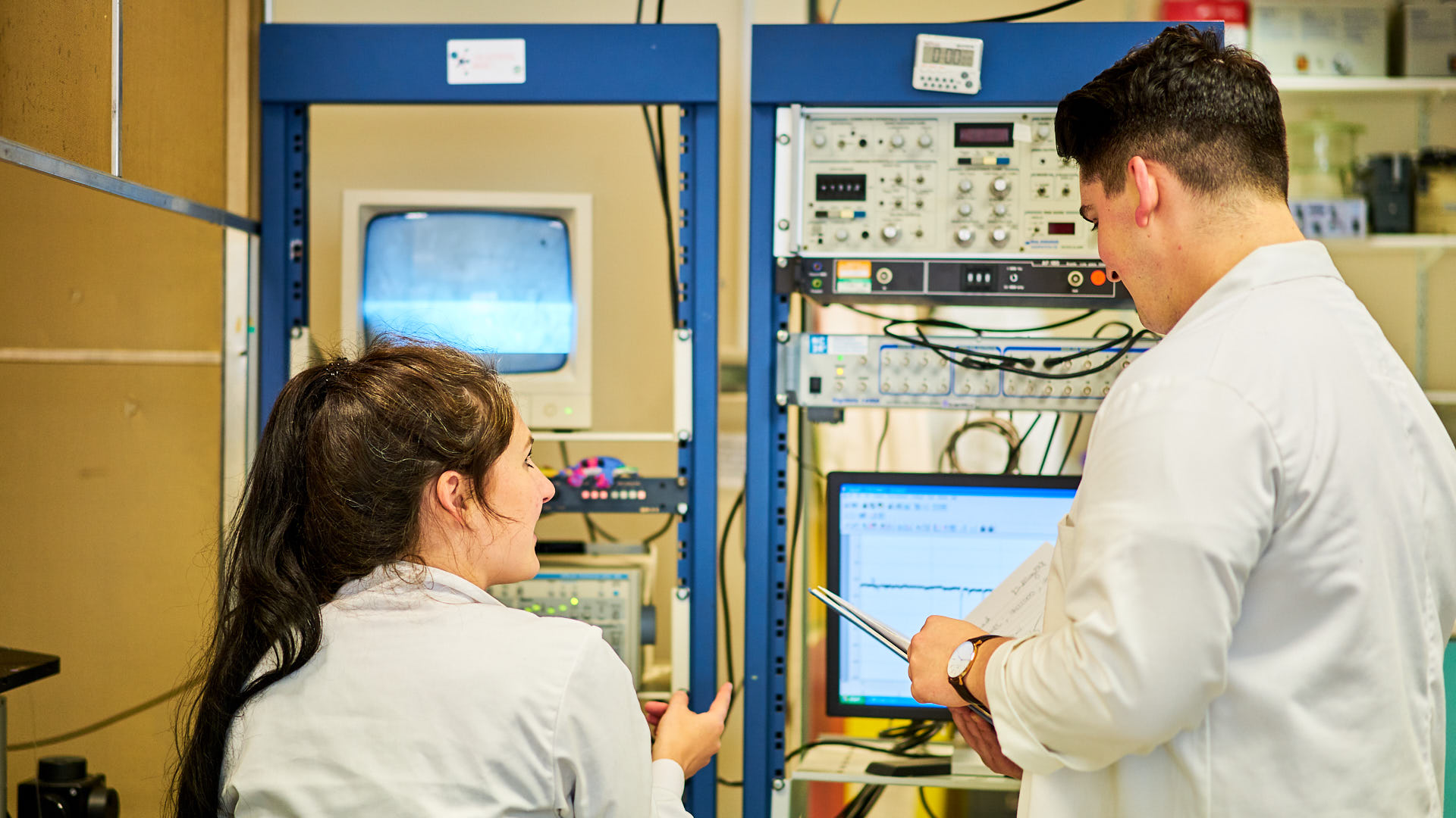 Two PhD students working on research in a lab