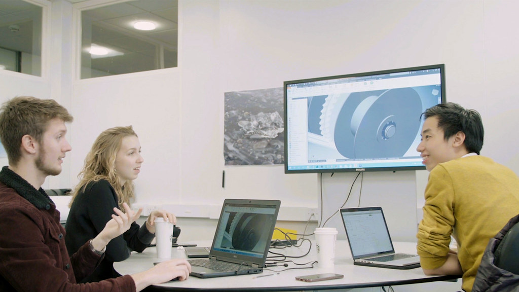 Three students discuss their shaft design in front of a large screen with a CAD image