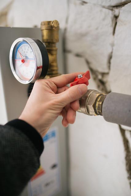 Heating boiler repair. Hand on valve closeup.